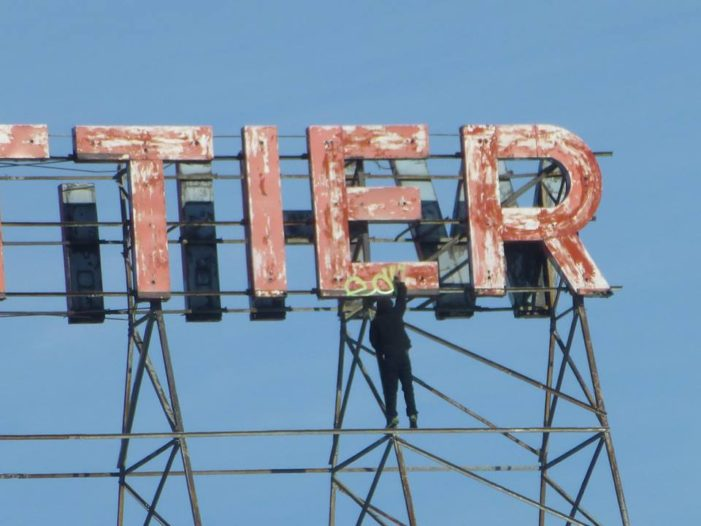 Graffiti vandal defaces iconic sign atop historic Whittier near downtown Detroit in daylight