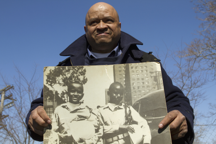 Colbert Prince, who lived at the housing units in the 1950s and '60s, poses with a photo of himself and a friend.