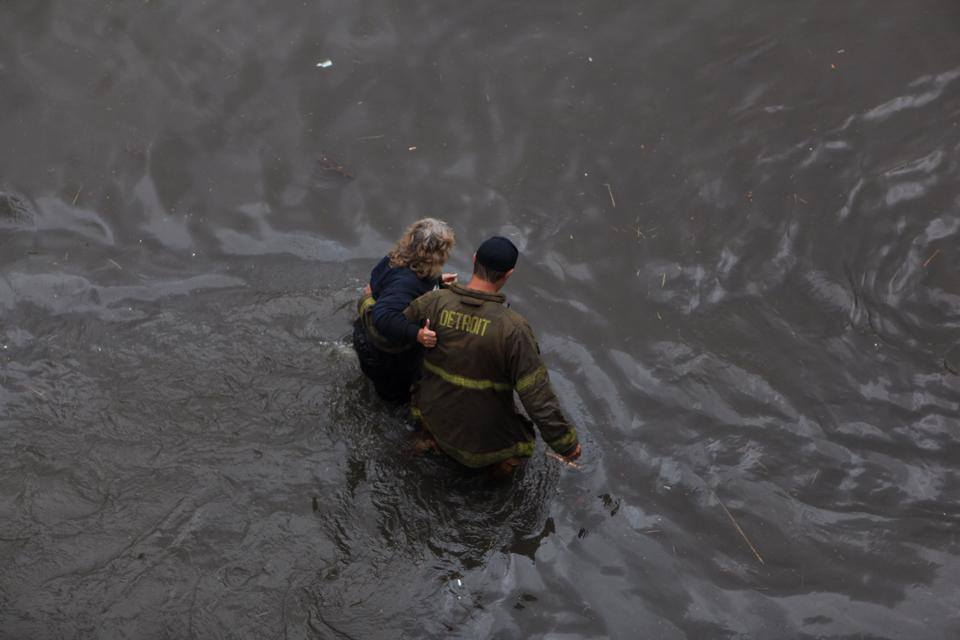 A Detroit firefighter rescues a woman after I-75 flooded.