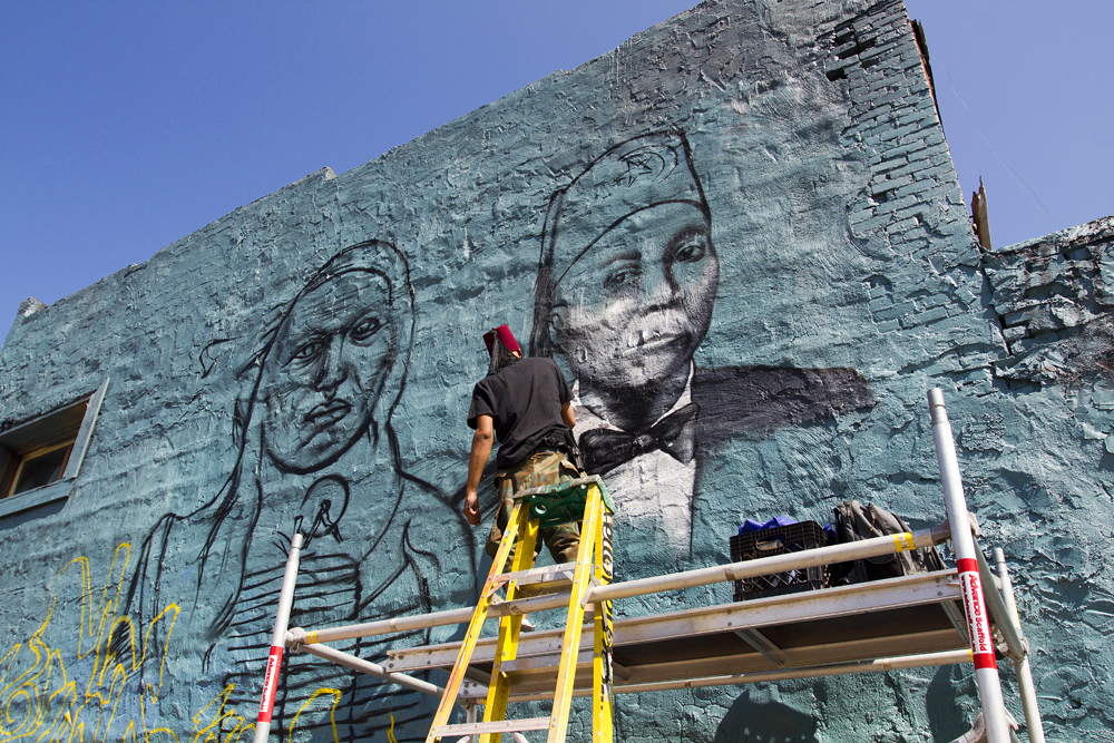 Detroit artist Sintex paints over a tribute to Vincent Chin.