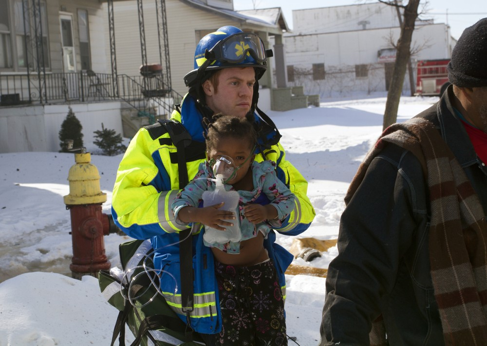 A paramedic carries an injured toddler to an ambulance. All photos by Steve Neavling.