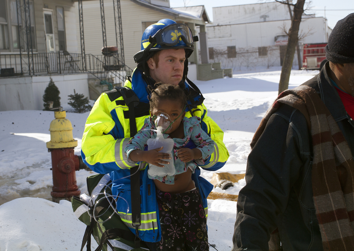A medic carries a toddler injured in the Marcus St. fire. Photo by Steve Neavling.
